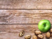 Apple και υπόβαθρο καρυδιών Ξηρά ξύλα καρυδιάς με το aple σε ένα ξύλινο υπόβαθρο Στοκ Φωτογραφία