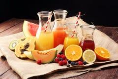 Apple και χυμός από πορτοκάλι - διάφορα μπουκάλια με τους χυμούς φρούτων και μούρων, εκλεκτής ποιότητας ξύλινο υπόβαθρο, εκλεκτικ Στοκ Φωτογραφίες