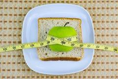 Apple και ψωμί που εξυπηρετούνται στο άσπρο πιάτο με τη μέτρηση της ταινίας Στοκ φωτογραφία με δικαίωμα ελεύθερης χρήσης