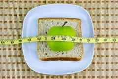 Apple και ψωμί που εξυπηρετούνται στο άσπρο πιάτο με τη μέτρηση της ταινίας Στοκ εικόνες με δικαίωμα ελεύθερης χρήσης