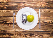 Apple και glucometer για να μετρήσει τη ζάχαρη αίματος σε ένα πιάτο, η έννοια της σωστής υγιεινής διατροφής Στοκ Εικόνες