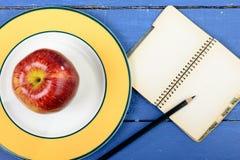 Apple και notebookwith μολύβι σε έναν πίνακα Στοκ Φωτογραφία