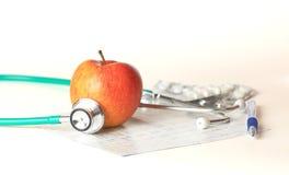Apple και stetoskop σε ένα άσπρο υπόβαθρο Στοκ φωτογραφία με δικαίωμα ελεύθερης χρήσης