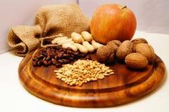 Apple, καρύδια και σπόροι που βρίσκονται σε ένα ξύλινο γραφείο Στοκ φωτογραφία με δικαίωμα ελεύθερης χρήσης