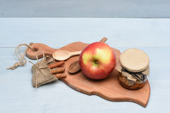 Apple, καρύδια στο βάζο γυαλιού στον τέμνοντα πίνακα Στοκ Εικόνα