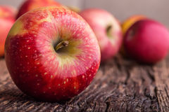 Apple Κόκκινα μήλα σε άλλες θέσεις στον ξύλινο πίνακα Στοκ Φωτογραφίες