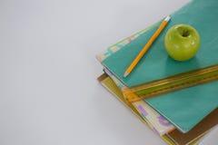 Apple, κλίμακα και μολύβι στο σωρό βιβλίων Στοκ εικόνα με δικαίωμα ελεύθερης χρήσης