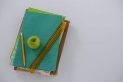 Apple, κλίμακα και μολύβι στο σωρό βιβλίων Στοκ Φωτογραφία