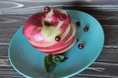Apple με ένα το βακκίνιο και τα φύλλα της μέντας σε ένα πιάτο Στοκ εικόνα με δικαίωμα ελεύθερης χρήσης