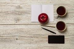 Apple με ένα φλυτζάνι του τσαγιού και ενός τηλεφώνου Στοκ Φωτογραφίες