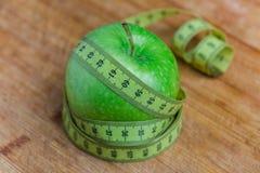 Apple με μια μετρώντας ταινία γύρω, την έννοια της διατροφής και την απώλεια βάρους Στοκ Φωτογραφία