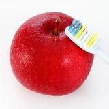 Apple με μια οδοντόβουρτσα, στο λευκό οδοντικές έννοιες προσοχής Στοκ Φωτογραφία