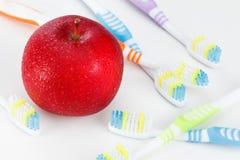 Apple με μια οδοντόβουρτσα, στο λευκό οδοντικές έννοιες προσοχής Στοκ Εικόνες