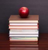 Apple με τα βιβλία στο ξύλινο γραφείο Στοκ φωτογραφία με δικαίωμα ελεύθερης χρήσης