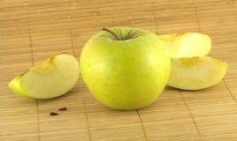 Apple με τα κομμάτια στο ψάθινο χαλί Στοκ εικόνες με δικαίωμα ελεύθερης χρήσης