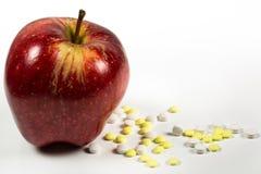 Apple με τα μέρη των ιατρικών χαπιών στην πλευρά Στοκ εικόνες με δικαίωμα ελεύθερης χρήσης