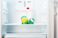 Apple με τη μέτρηση της ταινίας και του μπουκαλιού στο ράφι του ψυγείου Στοκ Φωτογραφίες