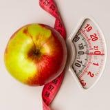 Apple με τη μέτρηση της ταινίας στην κλίμακα βάρους dieting Στοκ Εικόνα