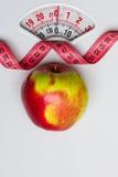 Apple με τη μέτρηση της ταινίας στην κλίμακα βάρους dieting Στοκ εικόνα με δικαίωμα ελεύθερης χρήσης