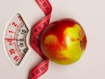 Apple με τη μέτρηση της ταινίας στην κλίμακα βάρους dieting Στοκ Φωτογραφία