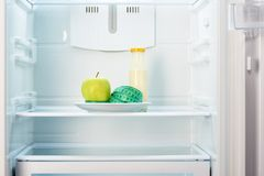 Apple με τη μέτρηση της ταινίας στο άσπρο πιάτο με το μπουκάλι Στοκ Φωτογραφίες