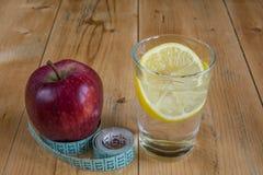 Apple με τη μέτρηση του ποτού ταινιών και νερού με το λεμόνι Στοκ εικόνες με δικαίωμα ελεύθερης χρήσης