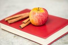 Apple με το βιβλίο και τα ξηρά φύλλα Στοκ Φωτογραφία