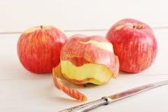 Apple με το καθαρισμένο δέρμα και ένα μαχαίρι Στοκ εικόνες με δικαίωμα ελεύθερης χρήσης