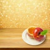 Apple με το μέλι στον ξύλινο πίνακα πέρα από το χρυσό υπόβαθρο bokeh Εβραϊκή νέα έννοια Rosh Hashanah διακοπών έτους Στοκ Φωτογραφία