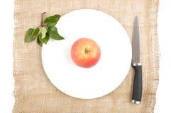 Apple με το μαχαίρι και φύλλα στη γιούτα Στοκ εικόνες με δικαίωμα ελεύθερης χρήσης