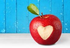 Apple με το χαρασμένο σημάδι καρδιών στο ξύλινο υπόβαθρο Στοκ εικόνα με δικαίωμα ελεύθερης χρήσης