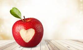Apple με το χαρασμένο σημάδι καρδιών στο ξύλινο υπόβαθρο Στοκ φωτογραφίες με δικαίωμα ελεύθερης χρήσης