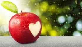 Apple με το χαρασμένο σημάδι καρδιών στο υπόβαθρο Στοκ εικόνες με δικαίωμα ελεύθερης χρήσης