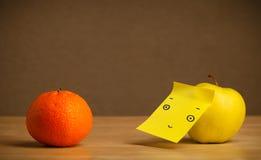 Apple με post-it τη σημείωση που εξετάζει το πορτοκάλι Στοκ φωτογραφία με δικαίωμα ελεύθερης χρήσης