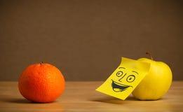 Apple με post-it τη σημείωση που χαμογελά στο πορτοκάλι Στοκ φωτογραφία με δικαίωμα ελεύθερης χρήσης