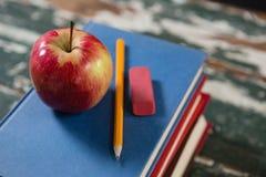 Apple, μολύβι και γόμα στο σωρό των βιβλίων Στοκ φωτογραφία με δικαίωμα ελεύθερης χρήσης