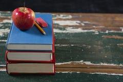 Apple, μολύβι και γόμα στο σωρό των βιβλίων Στοκ Εικόνες