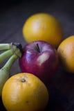 Apple, μπανάνες και πορτοκάλια πέρα από τον ξύλινο πίνακα Στοκ Εικόνες