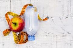 Apple, μπουκάλι νερό και μέτρηση της ταινίας στο άσπρο υπόβαθρο Στοκ φωτογραφία με δικαίωμα ελεύθερης χρήσης