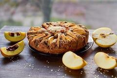 Apple ξινή με το κυδώνι, τους σπόρους παπαρουνών, τις σταφίδες και το σουσάμι στον ξύλινο καφετή πίνακα Πίτα της Apple που διακοσ Στοκ Φωτογραφία