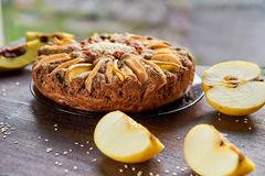 Apple ξινή με το κυδώνι, τους σπόρους παπαρουνών, τις σταφίδες και το σουσάμι στον ξύλινο καφετή πίνακα Πίτα της Apple που διακοσ Στοκ εικόνα με δικαίωμα ελεύθερης χρήσης