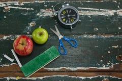 Apple, ξυπνητήρι, ξεσκονόπανο, ψαλίδι και κιμωλία στον ξύλινο πίνακα Στοκ φωτογραφία με δικαίωμα ελεύθερης χρήσης