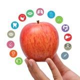 Apple που κρατά υπό εξέταση με τα εικονίδια υγείας γύρω Στοκ φωτογραφίες με δικαίωμα ελεύθερης χρήσης
