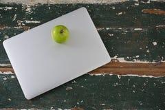Apple που κρατιέται στο lap-top Στοκ Εικόνα