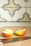 Apple που τεμαχίζεται στο μισό με την κουζίνα Στοκ φωτογραφίες με δικαίωμα ελεύθερης χρήσης