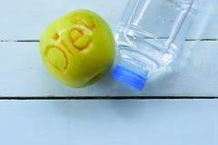 Apple που χαράζει τη διατροφή και το μπουκάλι νερό χαρακτήρα στο μπλε υπόβαθρο Τοπ όψη Στοκ φωτογραφία με δικαίωμα ελεύθερης χρήσης