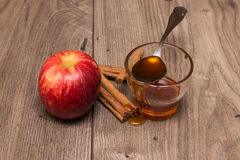 Apple, ραβδιά κανέλας, και ένα γυαλί με το μέλι Στοκ εικόνα με δικαίωμα ελεύθερης χρήσης