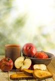Apple, ρόδι, κροτίδες στον πίνακα ενάντια στις ακτίνες ήλιων Στοκ Εικόνα