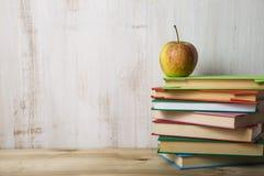 Apple σε έναν σωρό των βιβλίων σε έναν ελαφρύ ξύλινο πίνακα Στοκ Εικόνες