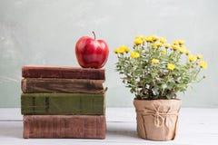 Apple σε έναν σωρό των βιβλίων στον πίνακα με τα λουλούδια Στοκ Εικόνες